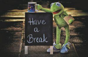 Frosch Kermit macht eine Pause und isst einen kleinen Snack