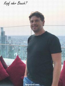 Mann auf einer Dachterrasse, im Hintergrund Hochhäuser
